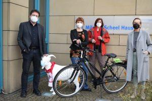 """Der Verein Endlich"""" nimmt vor dem Dr. Mildred Scheel Haus Fahrrad in Empfang."""